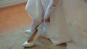 Νύφη που βάζει στα άσπρα παπούτσια της απόθεμα βίντεο