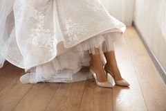 Νύφη που βάζει στα γαμήλια παπούτσια στο σπίτι όπου παίρνει έτοιμη - φορώντας το άσπρο φόρεμα σε ένα φωτεινό δωμάτιο με ξύλινο στοκ εικόνα με δικαίωμα ελεύθερης χρήσης