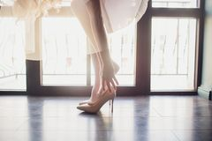 Νύφη που βάζει στα παπούτσια της Οι λεπτομέρειες κάνουν τη διαφορά ενάντια στα πανοραμικά παράθυρα υποβάθρου στοκ εικόνα