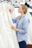 Νύφη που εξετάζει τη τιμή στο γαμήλιο φόρεμα στη νυφική μπουτίκ Στοκ Φωτογραφία