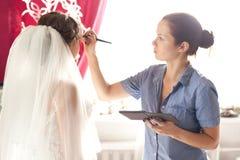 Νύφη που εφαρμόζει τη γαμήλια σύνθεση στοκ φωτογραφίες
