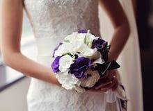Νύφη που κρατά μια ανθοδέσμη στα χέρια των πορφυρών λουλουδιών Στοκ φωτογραφίες με δικαίωμα ελεύθερης χρήσης