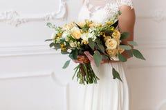 Νύφη που κρατά μια ανθοδέσμη των λουλουδιών σε ένα αγροτικό ύφος, γαμήλια ανθοδέσμη Στοκ Εικόνα