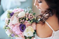 Νύφη που κρατά μια ανθοδέσμη των λουλουδιών στο αγροτικό ύφος, γάμος Στοκ Φωτογραφία