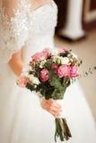 Νύφη που κρατά μια όμορφη ανθοδέσμη του τριαντάφυλλου και των άσπρων λουλουδιών Στοκ Φωτογραφίες