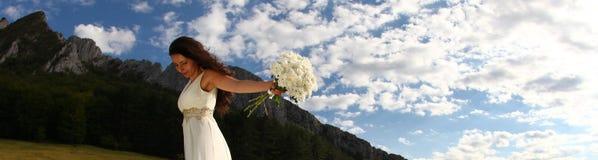 Νύφη που κρατά την άσπρη ανθοδέσμη στη φύση Στοκ φωτογραφία με δικαίωμα ελεύθερης χρήσης