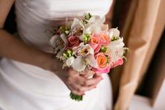 Νύφη που κρατά τη νυφική ανθοδέσμη κοντά επάνω ρόδινα και άσπρα τριαντάφυλλα, freesia, brunia που διακοσμείται στη σύνθεση Στοκ Φωτογραφίες
