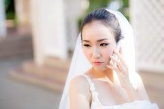 Νύφη που μιλά στο τηλέφωνο κυττάρων στο γαμήλιο φόρεμα Στοκ Εικόνα