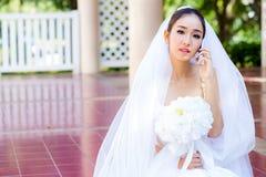 Νύφη που μιλά στο τηλέφωνο κυττάρων στο γαμήλιο φόρεμα Στοκ Φωτογραφία