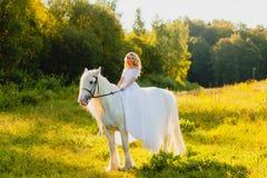 Νύφη που οδηγά ένα άλογο στο υπόβαθρο του ηλιοβασιλέματος Στοκ φωτογραφία με δικαίωμα ελεύθερης χρήσης