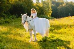 Νύφη που οδηγά ένα άλογο στο υπόβαθρο του ηλιοβασιλέματος Στοκ Φωτογραφία