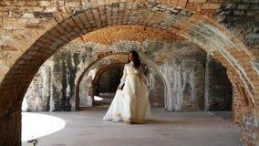 Νύφη που περπατά κάτω από τις αψίδες τούβλου απόθεμα βίντεο