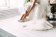 Νύφη που προσπαθεί στα γαμήλια παπούτσια στοκ φωτογραφίες