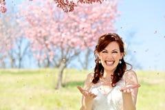 Νύφη που πλημμυρίζεται από τα πέταλα ανθών κερασιών Στοκ φωτογραφία με δικαίωμα ελεύθερης χρήσης