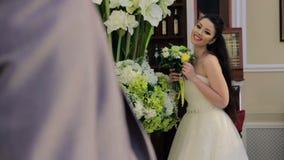 Νύφη που στέκεται κοντά στα λουλούδια και την ομιλία απόθεμα βίντεο