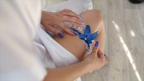 Νύφη που φορά γαμήλιο garter Η νύφη φορά garter στο πόδι Κινηματογράφηση σε πρώτο πλάνο της νέας νύφης που βάζει στον άσπρο ξύστη Στοκ Εικόνα