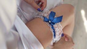 Νύφη που φορά γαμήλιο garter Η νύφη φορά garter στο πόδι Κινηματογράφηση σε πρώτο πλάνο της νέας νύφης που βάζει στον άσπρο ξύστη απόθεμα βίντεο