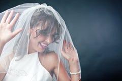 Νύφη που φορά το νυφικό πέπλο Στοκ Εικόνες
