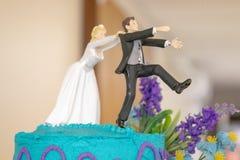 Νύφη που χαράζει τη γαμήλια διακόσμηση νεόνυμφων στο κέικ στοκ φωτογραφία