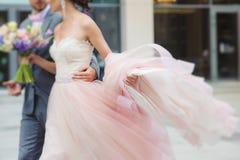 Νύφη πολυτέλειας που κρατά ένα πετώντας φόρεμα και ένα περπάτημα Στοκ Εικόνα