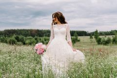 Νύφη σε ένα άσπρο φόρεμα και μια ανθοδέσμη των peonies στα χέρια στοκ εικόνα με δικαίωμα ελεύθερης χρήσης