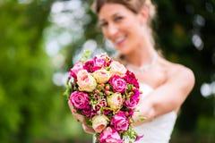 Νύφη στην εσθήτα με τη νυφική ανθοδέσμη Στοκ Φωτογραφία
