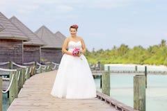 Νύφη στην τοποθέτηση γαμήλιων φορεμάτων κοντά στις βίλες νερού στοκ εικόνες με δικαίωμα ελεύθερης χρήσης