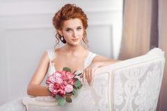 Νύφη στην όμορφη συνεδρίαση φορεμάτων που στηρίζεται στον καναπέ στο εσωτερικό στοκ εικόνες