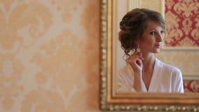 Νύφη στη ρόμπα μεταξιού που εξετάζει τον καθρέφτη, που προσπαθεί στα γαμήλια σκουλαρίκια της στο πρωί της ημέρας γάμου απόθεμα βίντεο