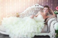 Νύφη στη συνεδρίαση γαμήλιων φορεμάτων στον καναπέ Στοκ φωτογραφία με δικαίωμα ελεύθερης χρήσης