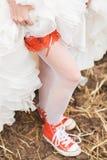 Νύφη στις άσπρες γυναικείες κάλτσες στα κόκκινα plimsolls Στοκ Εικόνες
