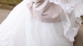 Νύφη στους άσπρους στροβίλους γαμήλιων φορεμάτων φιλμ μικρού μήκους