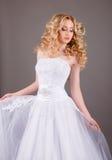 Νύφη στο άσπρο γαμήλιο φόρεμα σε ένα γκρίζο υπόβαθρο Στοκ Φωτογραφία