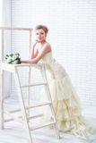 Νύφη στο γαμήλιο φόρεμα με τα λουλούδια και τη σκάλα Στοκ Φωτογραφίες