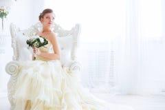 Νύφη στο γαμήλιο φόρεμα με τα λουλούδια και τη σκάλα Στοκ Φωτογραφία