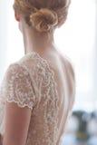 Νύφη στο γαμήλιο φόρεμα με τη δαντέλλα από την πλάτη στοκ φωτογραφίες