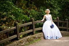 Νύφη στο γαμήλιο φόρεμα ομορφιάς που στέκεται στη γέφυρα Στοκ φωτογραφία με δικαίωμα ελεύθερης χρήσης