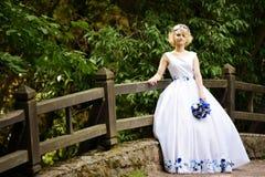 Νύφη στο γαμήλιο φόρεμα ομορφιάς που στέκεται στη γέφυρα Στοκ Εικόνες
