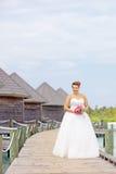 Νύφη στο γαμήλιο φόρεμα που κρατά μια δέσμη των λουλουδιών στοκ φωτογραφία
