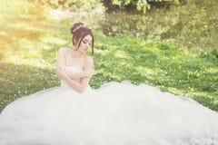 Νύφη στο πάρκο Ημέρα γάμου, μουντός ήλιος Καλοκαίρι στοκ φωτογραφία