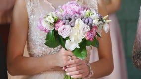 Νύφη στο φόρεμα δαντελλών που κρατά την όμορφη άσπρη ανθοδέσμη γαμήλιων λουλουδιών, κινηματογράφηση σε πρώτο πλάνο απόθεμα βίντεο