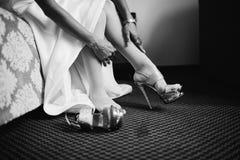 Νύφη στο φόρεμα στα άσπρα νυφικά παπούτσια Στοκ Εικόνες