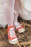 Νύφη στο φόρεμα στα βρώμικα κόκκινα plimsolls στο έδαφος Στοκ φωτογραφία με δικαίωμα ελεύθερης χρήσης
