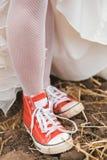 Νύφη στο φόρεμα στα κόκκινα plimsolls στο έδαφος Στοκ εικόνες με δικαίωμα ελεύθερης χρήσης