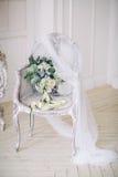Νύφη ` s bouqet σε μια όμορφη κλασική καρέκλα σε ένα άσπρο δωμάτιο Στοκ Φωτογραφίες