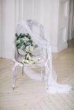 Νύφη ` s bouqet σε μια όμορφη κλασική καρέκλα σε ένα άσπρο δωμάτιο Στοκ φωτογραφία με δικαίωμα ελεύθερης χρήσης