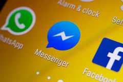 Νύχι του αντίχειρα/λογότυπο εφαρμογής αγγελιοφόρων Facebook σε ένα αρρενωπό smartphone στοκ εικόνες