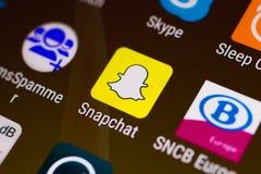 Νύχι του αντίχειρα/λογότυπο εφαρμογής Snapchat σε ένα αρρενωπό smartphone στοκ εικόνες
