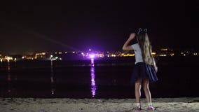 Νύχτα, ένα κορίτσι εφήβων σε μια λαμπρή φούστα χορεύει, άποψη από την πλάτη Ενάντια στα φω'τα της καμμένος πόλης επάνω από φιλμ μικρού μήκους
