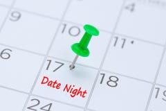 Νύχτα ημερομηνίας που γράφεται σε ένα ημερολόγιο με μια πράσινη καρφίτσα ώθησης στο remin στοκ εικόνα με δικαίωμα ελεύθερης χρήσης